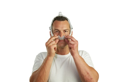 British Man fits nasal CPAP mask on his face